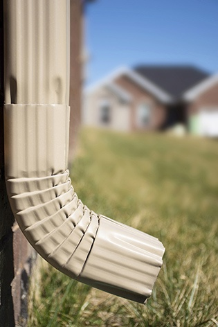 closeup of a light tan downspout on a brick home