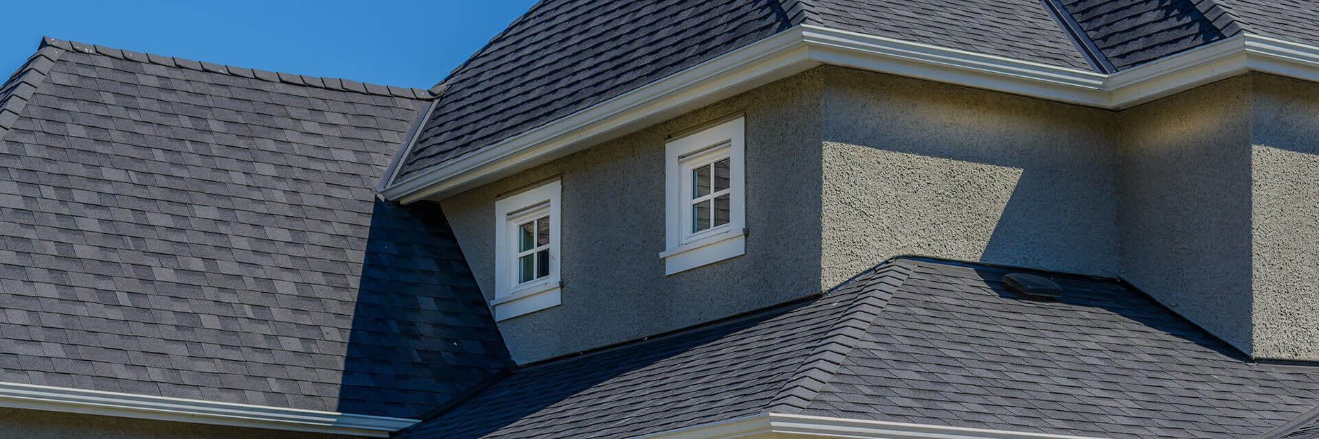 Photo of a gray asphalt shingle roof on a gray stucco house